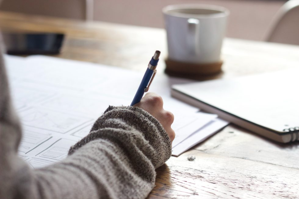 Person in sweater writing in a notebook
