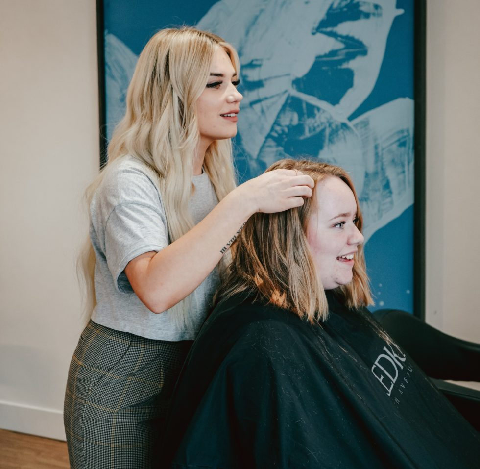 Woman styling another womans hair