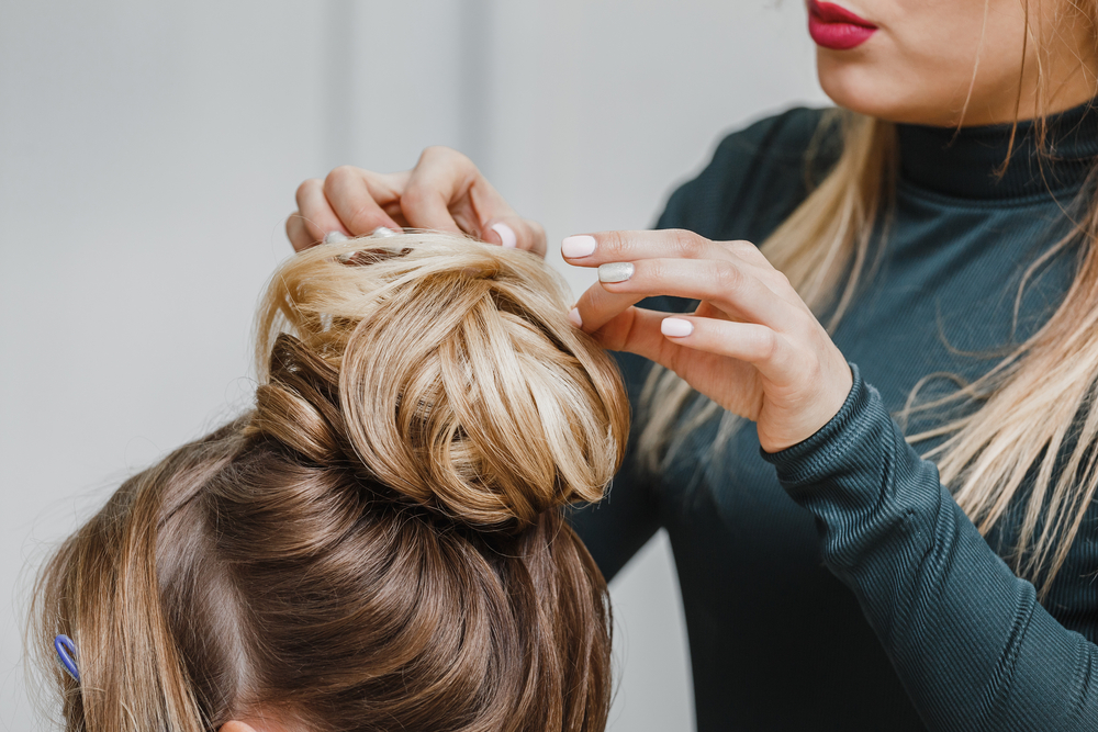 woman styling another woman's hair bun