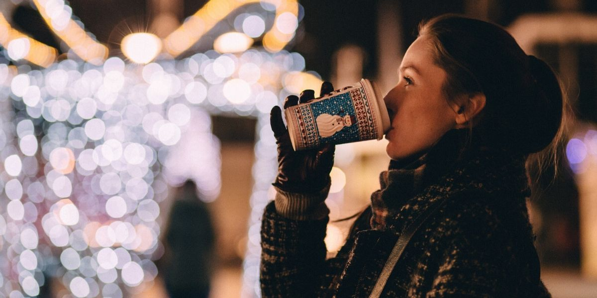 Woman drinking hot chocolate and looking at holiday lights
