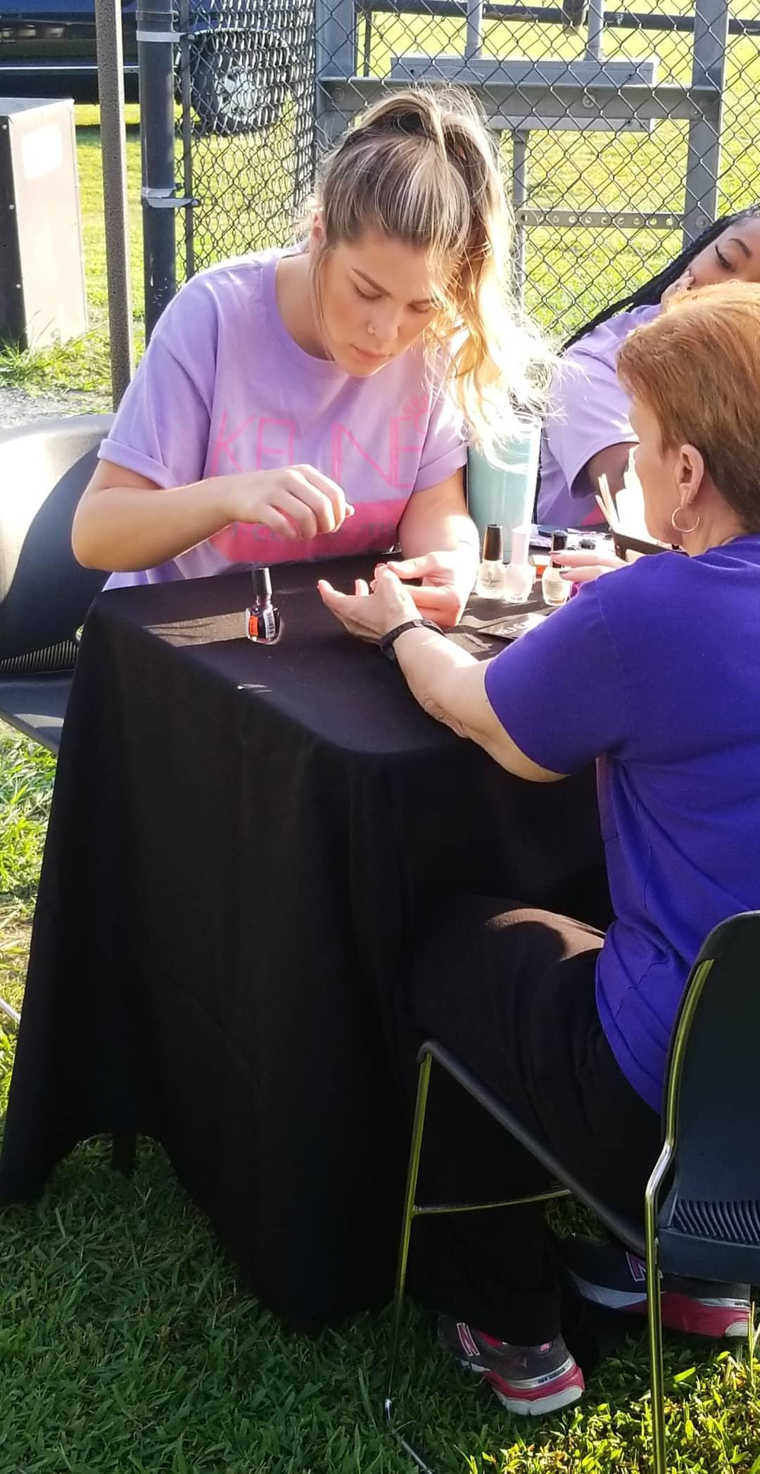 girl in purple shirt painting a woman's nails