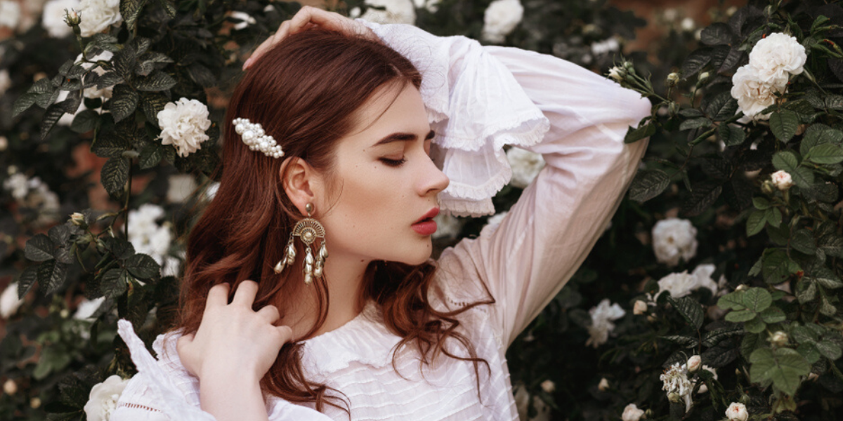 Brunette girl in a whit shirt and pearl barrette stands in front of white flowers.