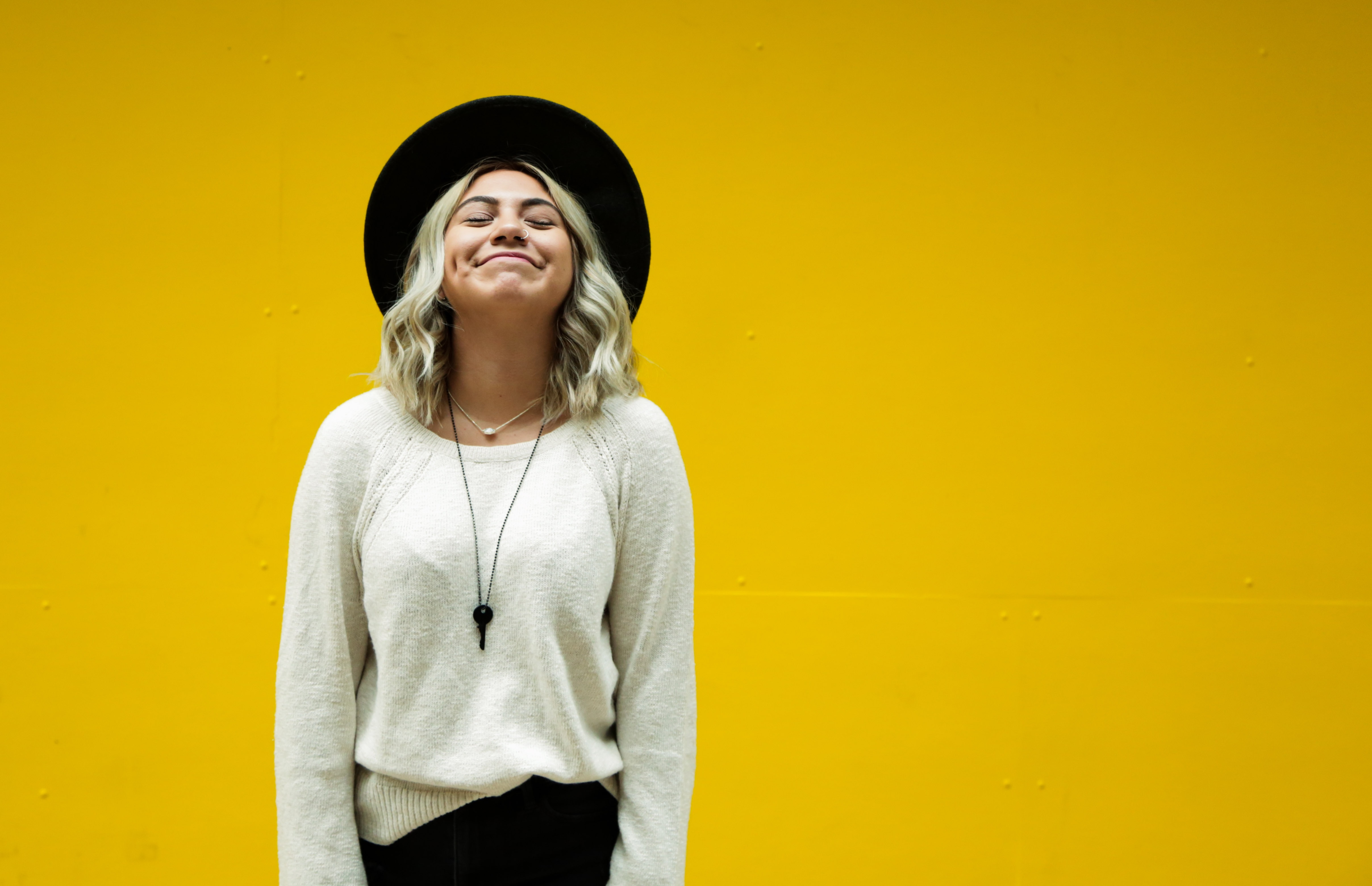 woman wearing white sweater smiling in front of a yellow wall