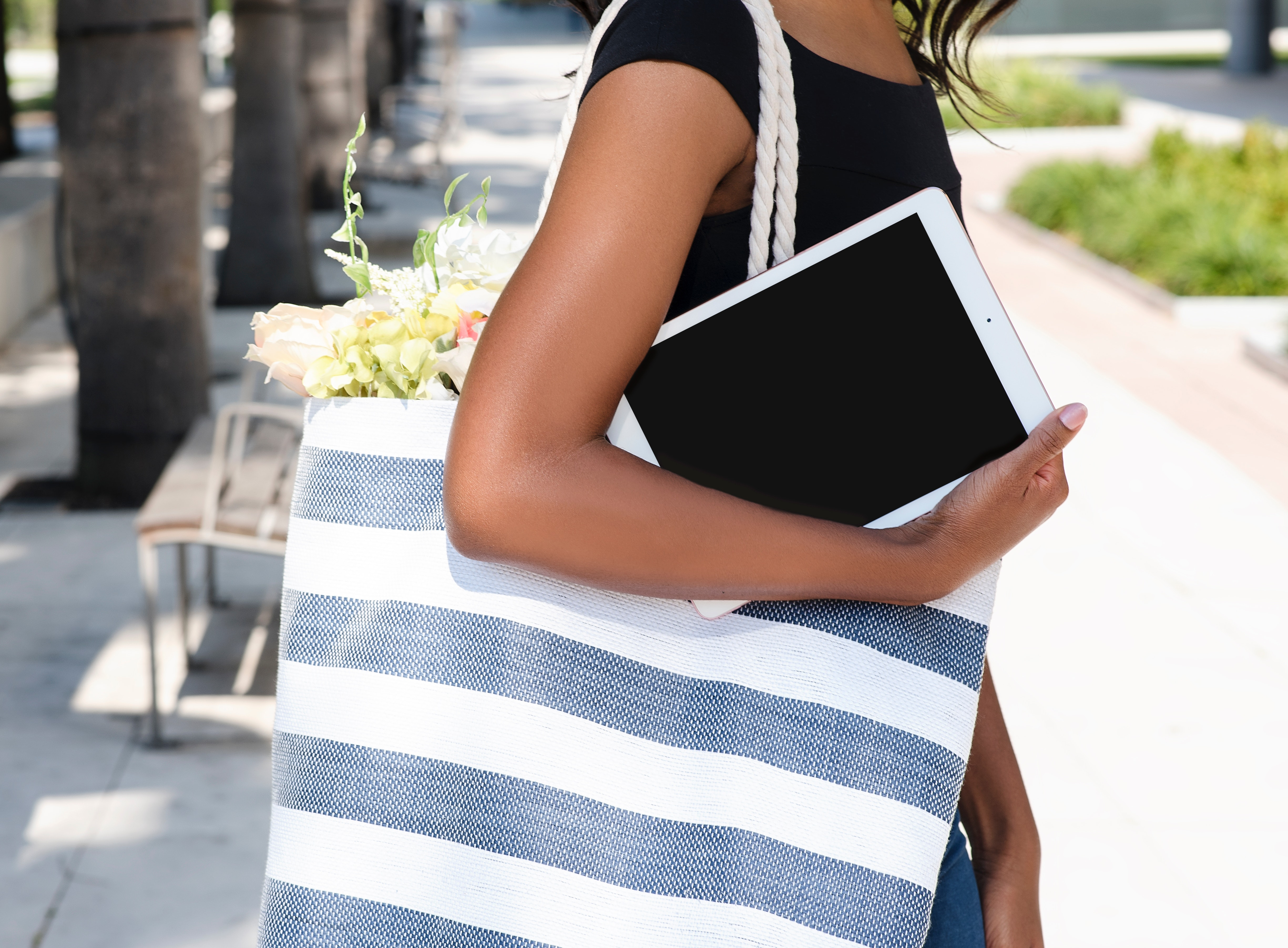woman carrying an ipad and a large tote bag