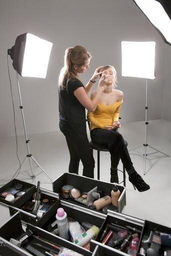woman doing another woman's makeup under spotlights