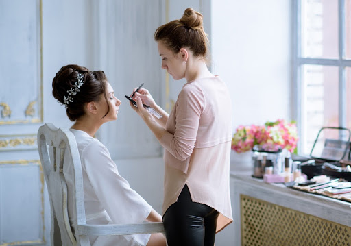 woman doing wedding makeup on another woman