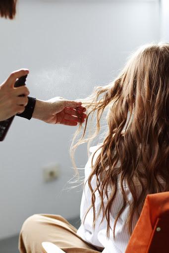 man hair spraying another woman's hair