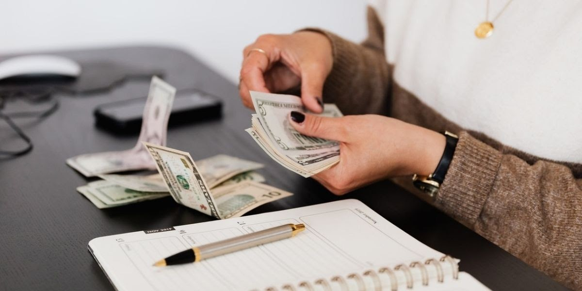 woman counting money with a planner